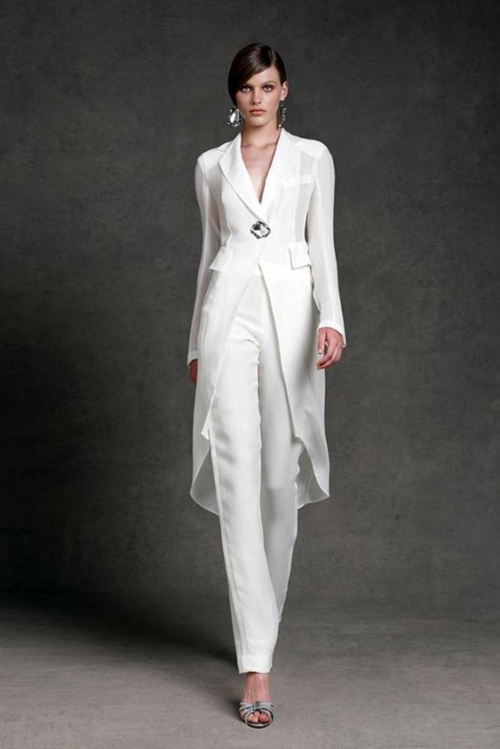 tenue mariage invité femme pantalon en tissu satiné blanc, veste longue en style redingote, veste fermée avec une grande broche au milieu, tailleur pantalon femme cocktail