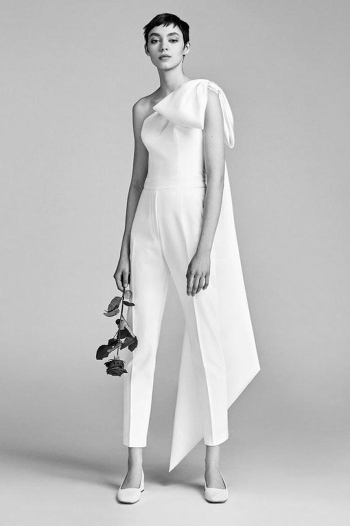 tenue ceremonie femme en blanc, top épaules asymétriques, une épaule décorée d'un gros nœud blanc avec un bout qui se prolonge jusqu'au sol