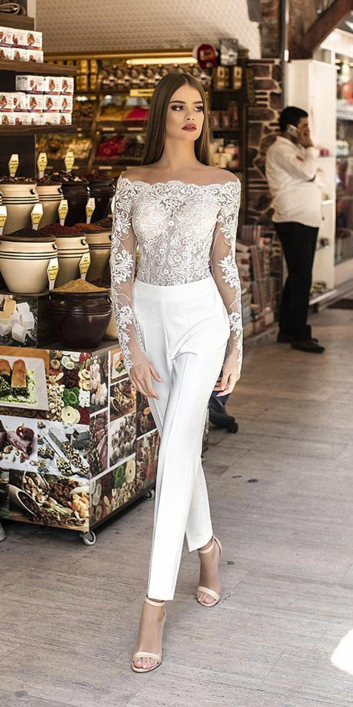 tailleur pantalon femme, tenue ceremonie femme, top moulant en dentelle blanche avec les manches en dentelle semi-transparentes, pantalon blanc taille haute a pinces, sandales talons aiguilles couleur ivoire