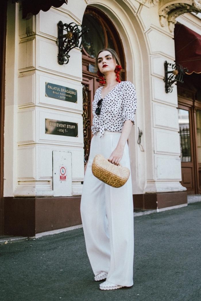 tenue d'été en pantalon large blanc avec top blanc à dots noirs et sac à main en paille, modèle de boucles d'oreilles massives en rouge