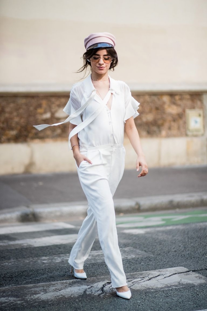 look moderne et chic en combinaison pantalon femme de couleur blanche aux manches courtes assortie avec chapeau rose pastel et chaussures blanches
