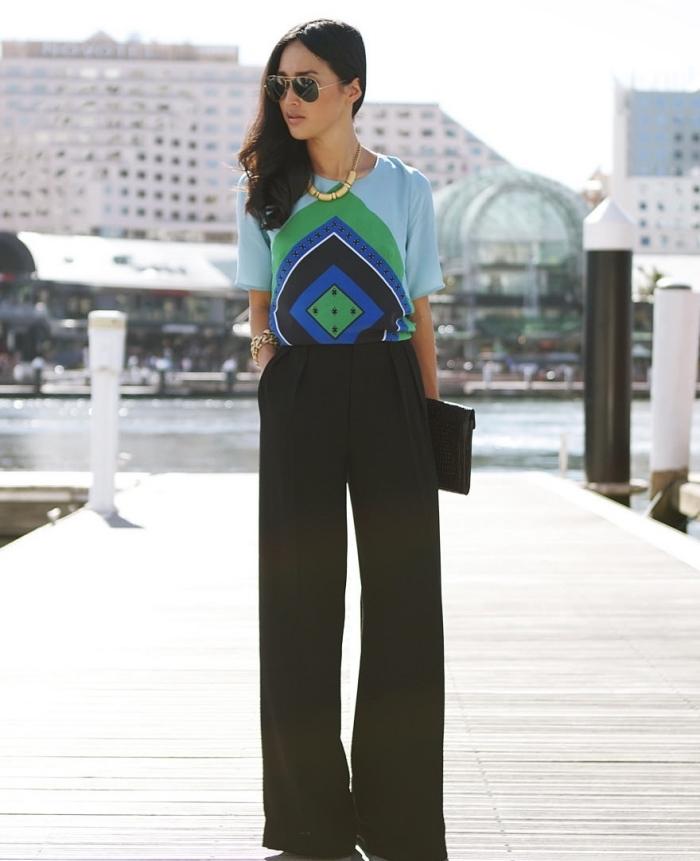 exemple de tailleur pantalon femme noir combiné avec blouse bleu clair aux motifs géométriques avec bracelet en or