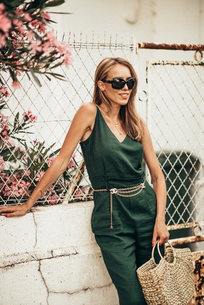 modèle de combinaison chic de couleur vert foncé combinée avec ceinture à design or et sac à main en paille