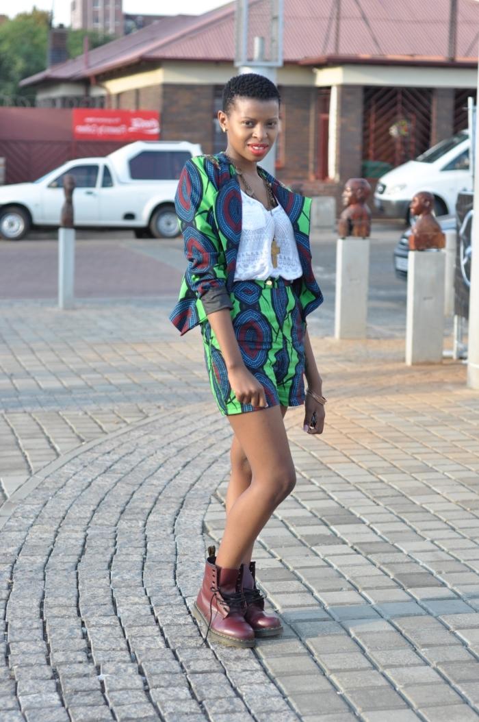 un ensemble deux pièces en tissu africain de short à taille haute et veste dans le même tissu combinés avec un top dentelle blanc et des bottines style grunge