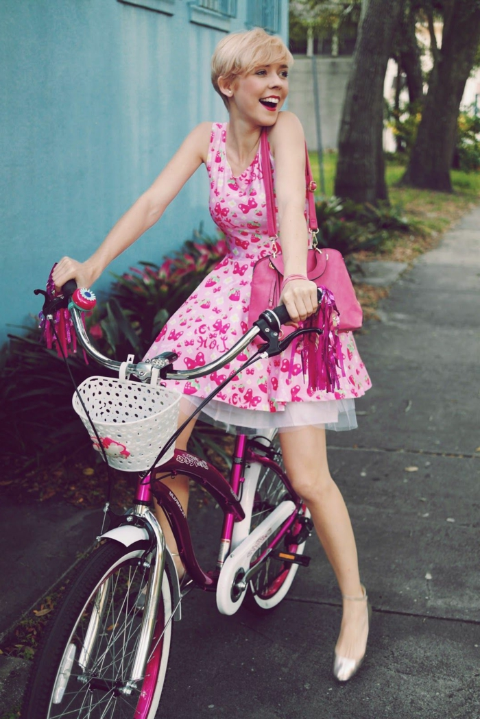 look annee 50, vélo couleur cyclamen, coupe courte, sac rose, robe guinguette aux cerisiers