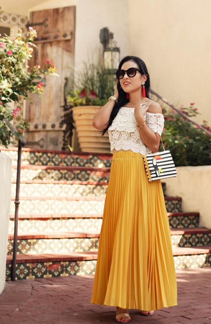 jupe longue taille haute, jupe jaune, blouse dentelle, petit sac rayé, lunettes de soleil et boucles d'oreilles franges