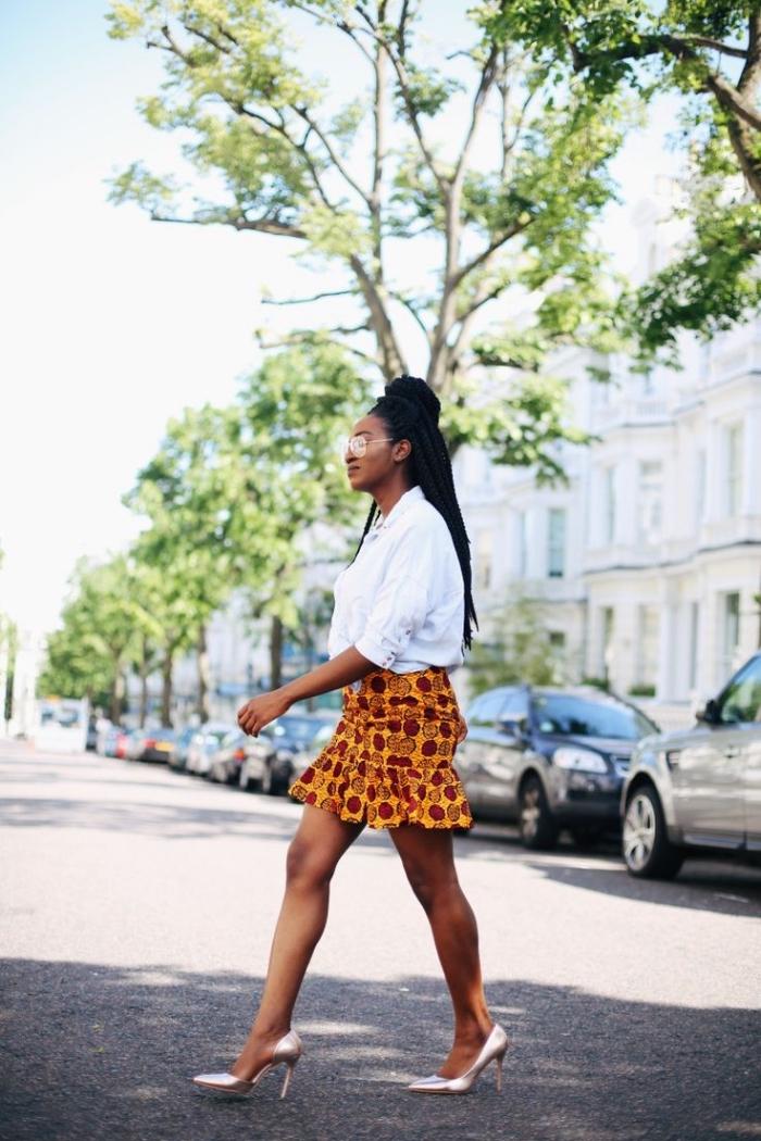 look ethnique chic en mini jupe wax volantée, combinée avec une chemise blanche classique et des escarpins métalliques