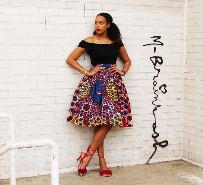 une jupe midi évasée à motif africain haut en couleur, combinée avec un top noir à épaules dénudées et des sandales à talons hauts rouge avec lacets montants