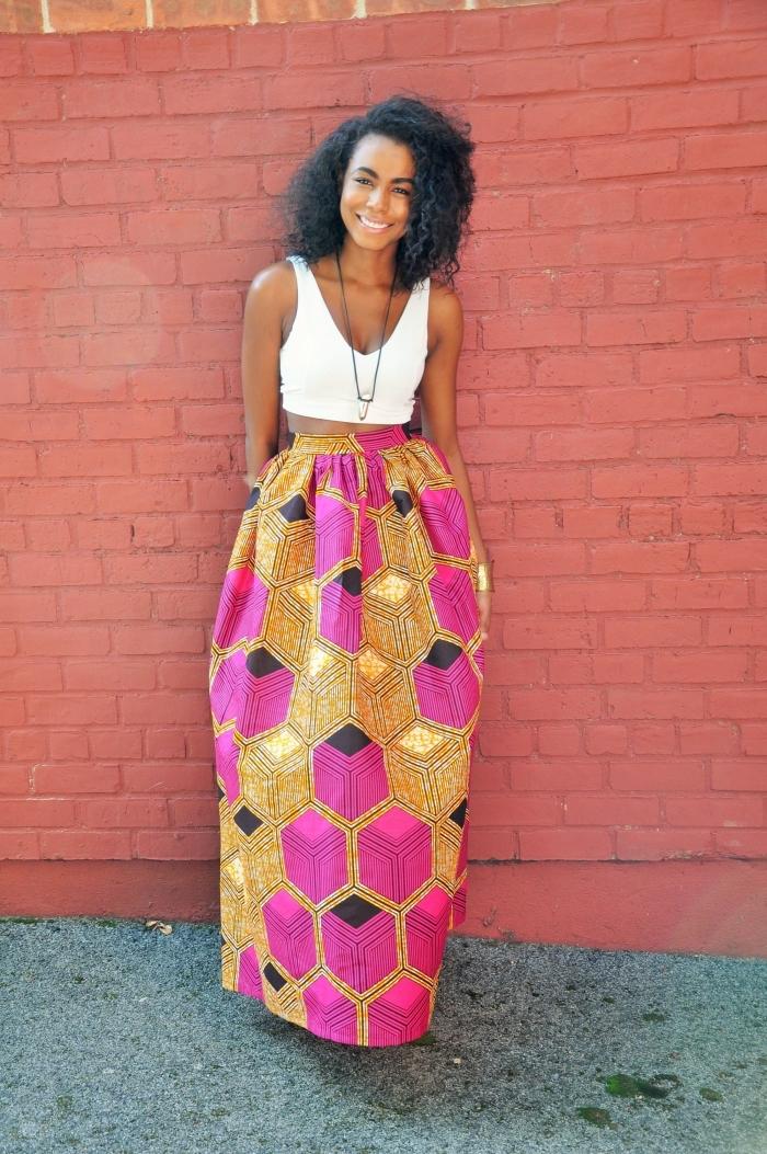 une allure bohème et romantique avec une maxi-jupe en tissu wax, ornée de motifs hexagones en rose et jaune moutarde, assortie avec un crop top blanc