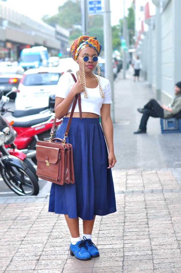 la mode africaine moderne, look vintage et chic en jupe midi bleu et crop top blanc, accessoirisés avec un attachée de foulard wax et un sac cartable en cuir marron