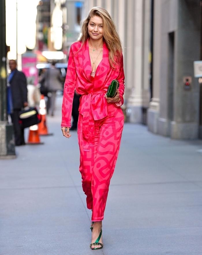 Gigi Hadid en combinaison pantalon femme habillée de couleur rose fuchsia combinée avec sandales et pochettes en vert