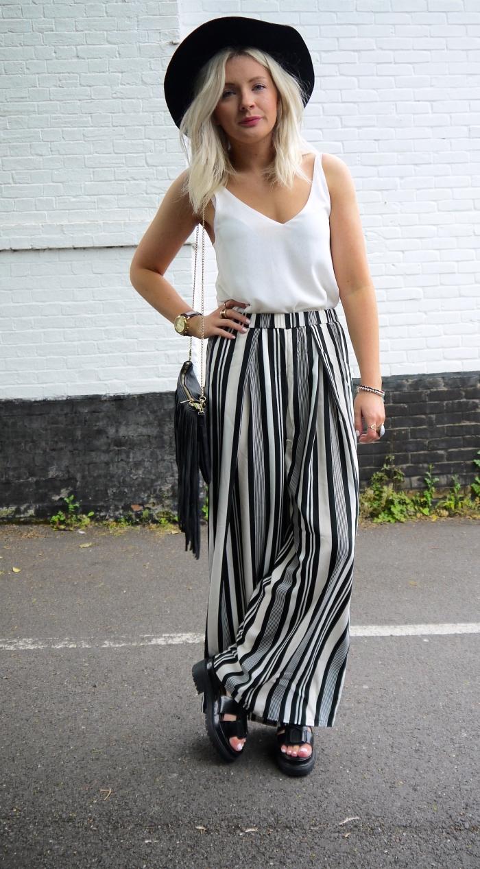 look bohème chic en blanc et noir avec pantalon fluide femme à design rayé et top à décolleté en V combiné avec capeline noire