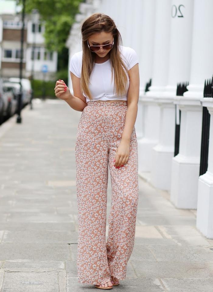 modèle de pantalon taille haute d'été de couleur beige aux motifs fleuris combiné avec t-shirt blanc enroulé