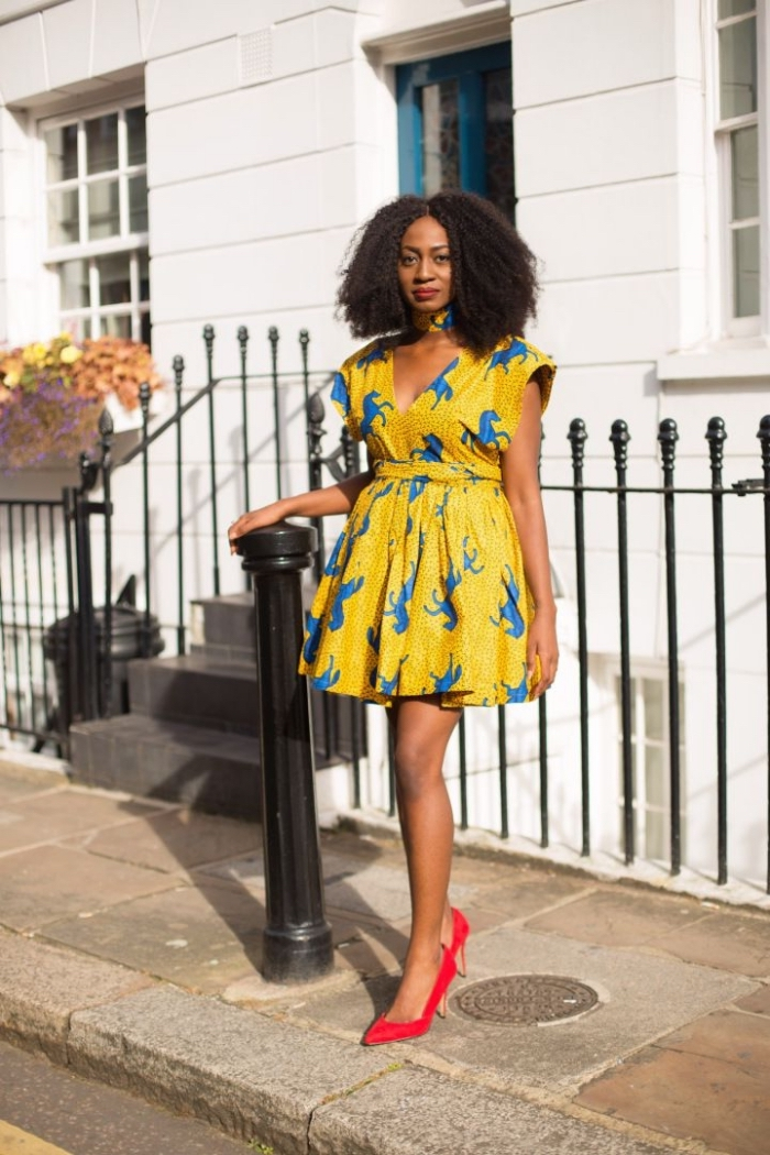 une jolie robe wax patineuse à motif cheval bleu sur fond jaune fluo et à taille cintrée associée à une paire d'escarpins rouge vermillon