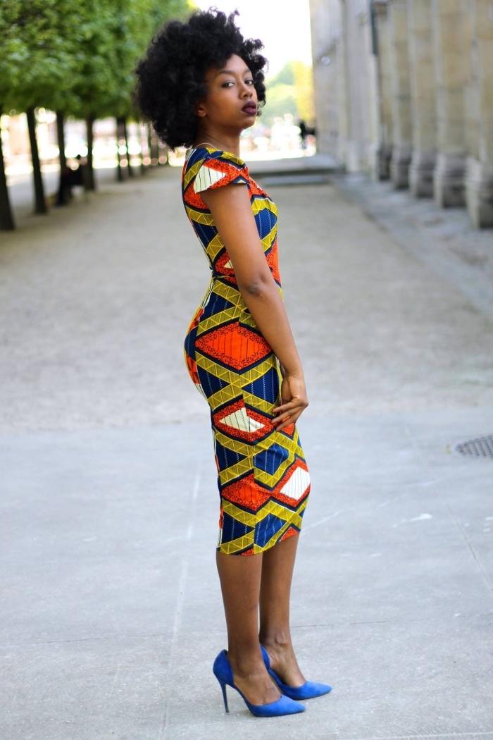 une robe moulante à motifs géométriques bariolés qui met en valeur les courbes féminines, assortie avec des escarpins bleu roi