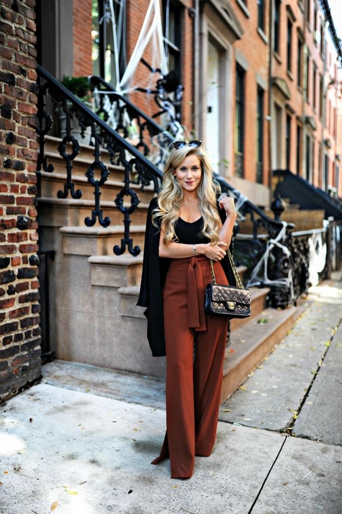 tenue en pantalon femme taille haute chic marron noué avec top noir et manteau long, coiffure de cheveux longs bouclés