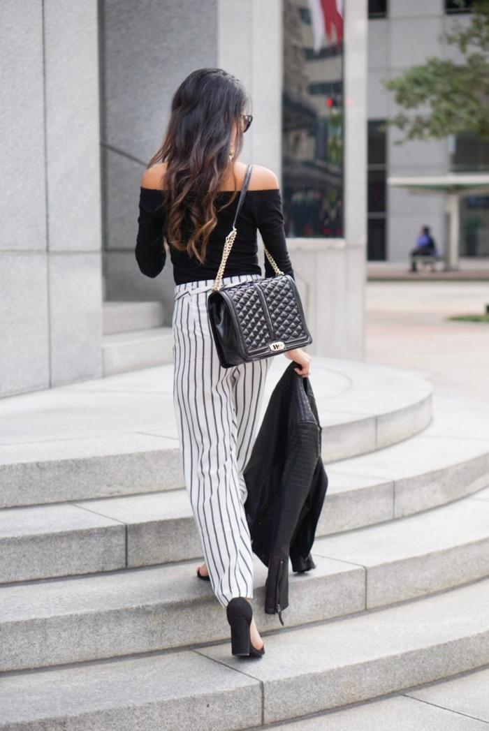 tenue élégante en blanc et noir avec pantalon à design rayé et blouse noire aux épaules dénudées, modèle de sac à main de cuir noir