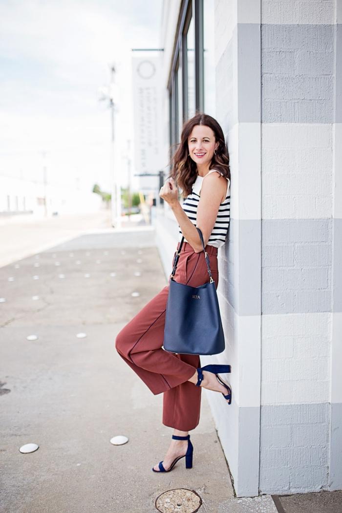 tenue casual smart en pantalon palazzo de couleur marron et top rayé en blanc et noir avec sac à main cuir bleu foncé