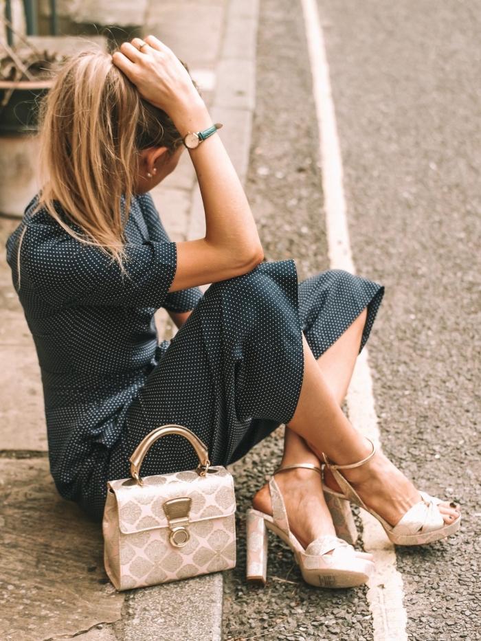 look féminin et chic en combinaison fluide femme à longueur genoux de couleur gris foncé à dots blancs portée avec sandales hautes