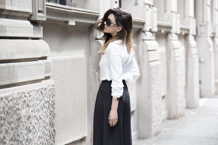 modèle de pantalon fluide femme été de couleur noir combiné avec chemise blanche et accessoires bracelet en or