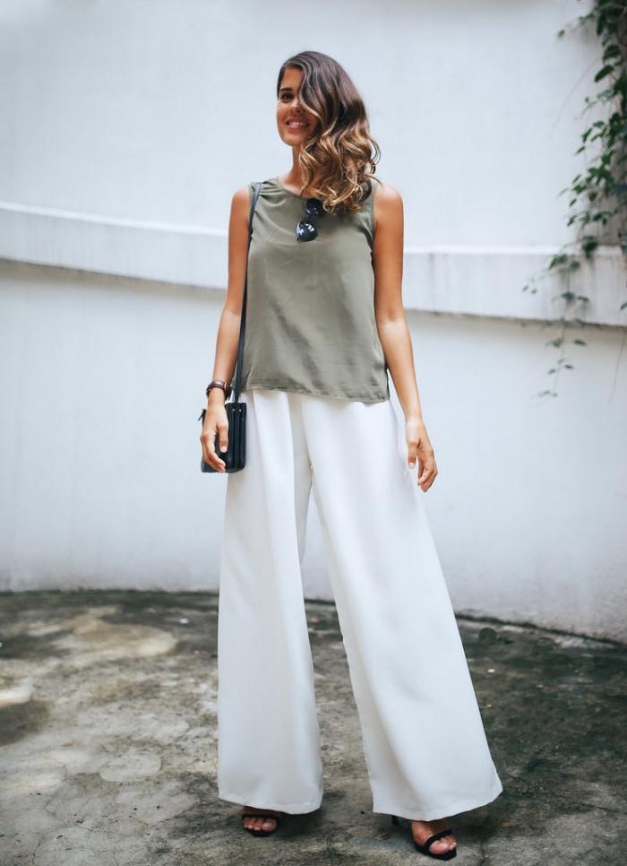 look élégant d'été en pantalon fluide blanc de taille haute avec top beige kaki, sac à main et sandales à talons noires