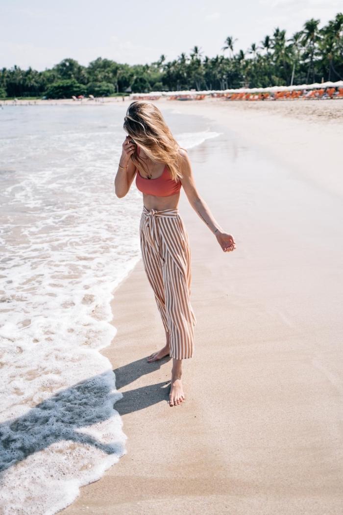 tenue de plage en pantalon rayé femme de style bohème en blanc et marron avec top crop corail et bracelet en or