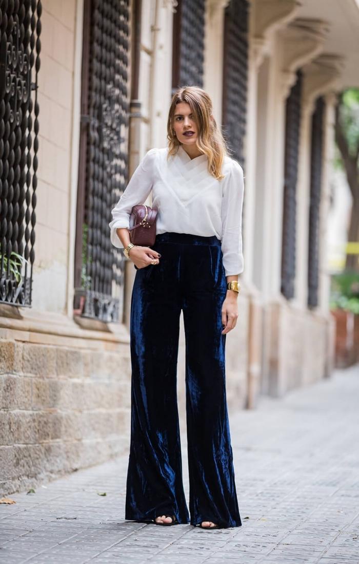 modèle de pantalon fluide femme en velours de couleur bleu foncé avec chemise blanche et sandales plates