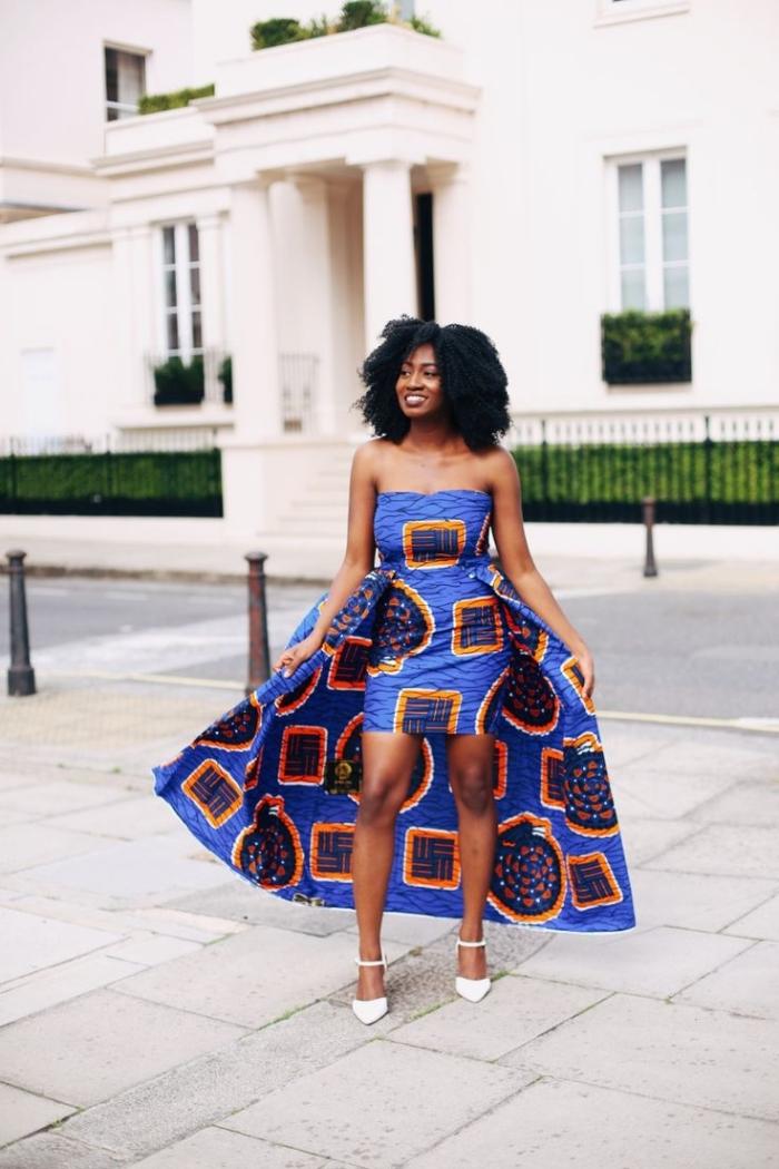 une robe africaine moderne aux épaules dénudées, avec traîne majestueuse dans le même tissu à motifs orange et bleu sur fond bleu roi