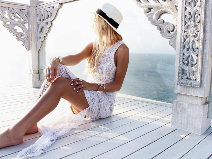 robe blanche boheme avec deux fentes latérales, robe sans manches, décolleté rond, femme cheveux longs blonds avec capeline blanche au nœud en tissu noir sur la tete