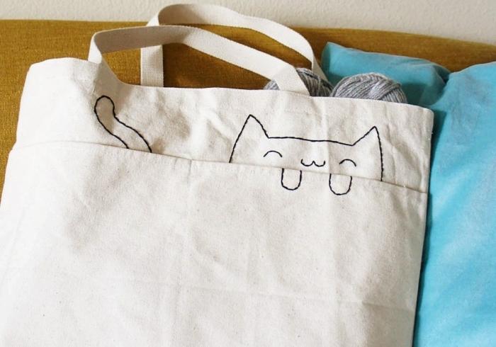 petite déco sur un tote bag blanc avec fil noir, idée broderie facile aux motifs visage et queue de chat sur un sac à main