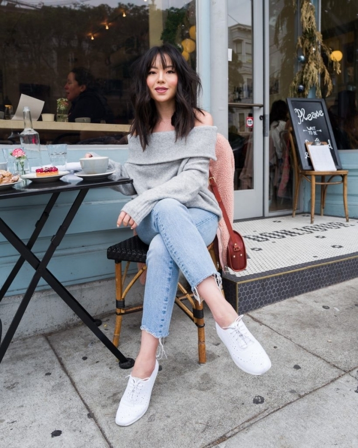 derby femme blancs portés avec une paire de jeans clairs et un pull gris à manches dénudées, look casual avec derbies