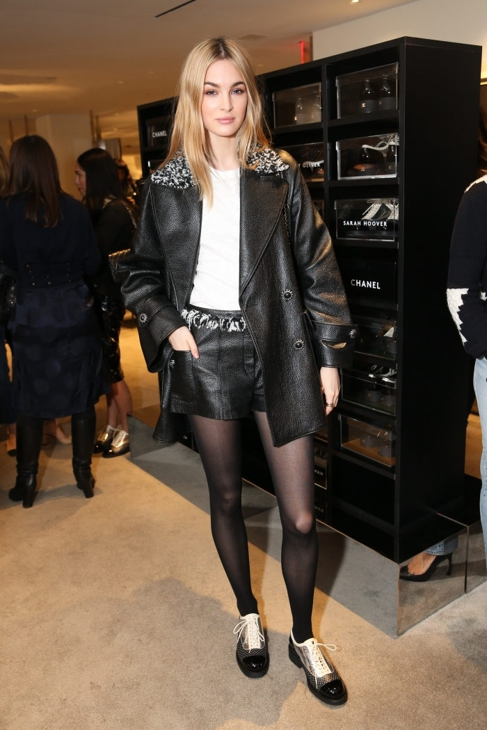modèle de chaussures à petits talons de Chanel, shorts en cuir combinés avec un top blanc et une paire de derbies noir et blanc à design métallique argenté