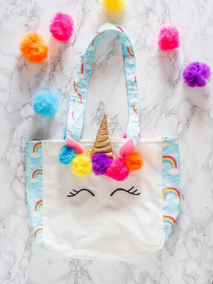 accessoire personnalisé avec un sac cabas toile blanc à design licorne aux motifs cils et accessoire de tête en pompons