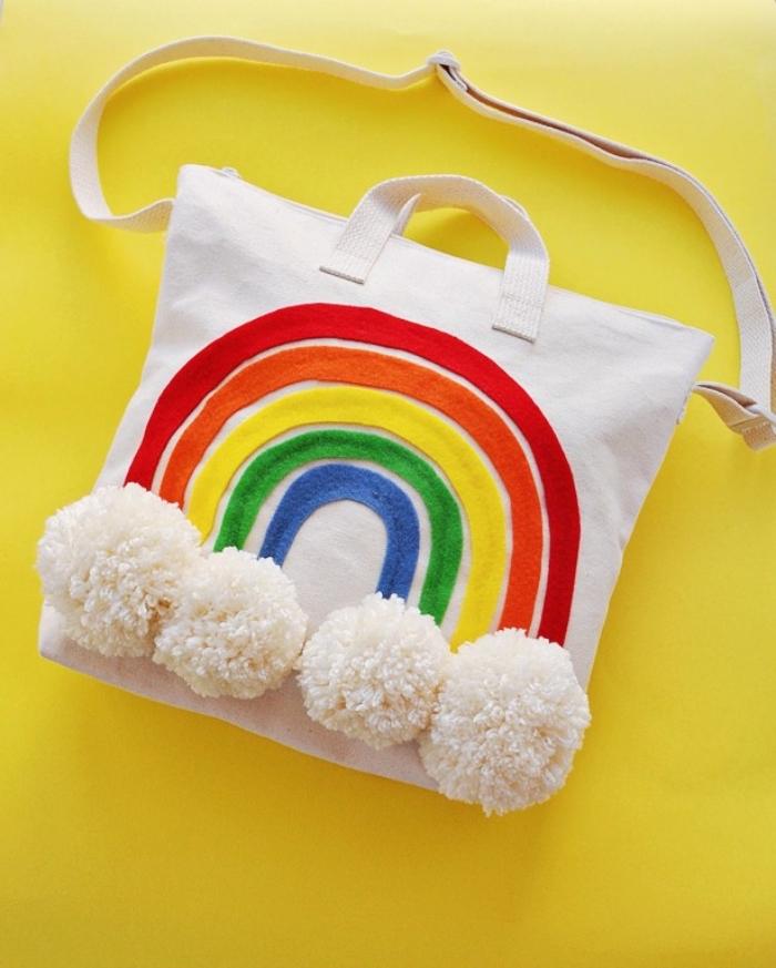 exemple de sac cabas personnalisé avec bandeau de tissu colorées à design arc en ciel et pompons en laine blancs