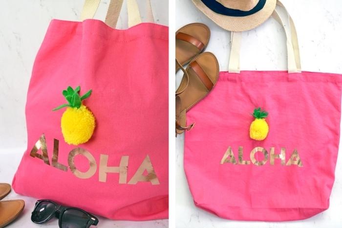 modèle de tote bag en tissu rose avec poignée beige et jolie déco en lettres dorés aloha avec petit anans en pompon jaune