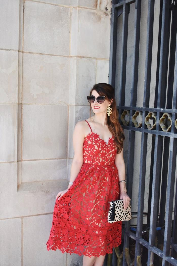 invitée de mariage près d'un grand portillon en fer, lunettes de soleil, sac tendance