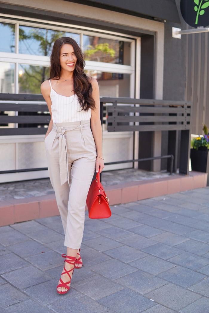 femme bien habillée en combinaison casual chic avec pantalon slim en beige et top rayé en blanc accessoirisé avec sandales et sac à main rouge