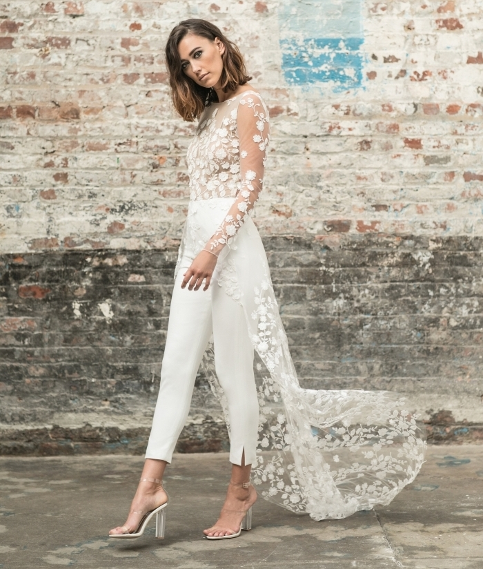 modèle de combi pantalon romantique en blanc avec pantalon slim et top à broderie florale aux manches longues et traîne