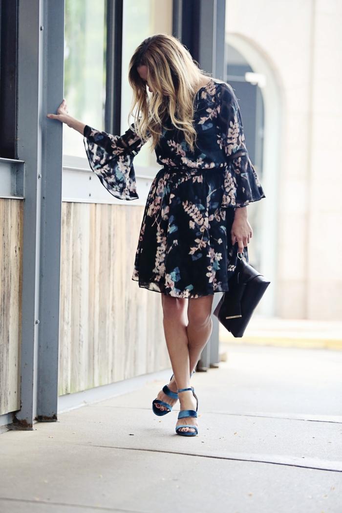 robe évasée noire aux fleurs, sandales bleues, sac noir, manches évasées