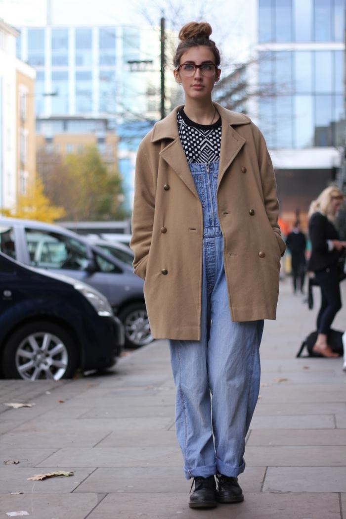 manteau camel, salopette bleue, chignon haut, fermeture boutonnière, pull motif graphique