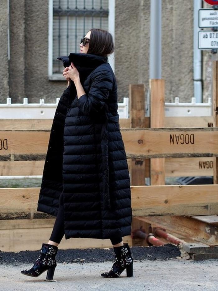 grand manteau noir, doudoune au col montant portée avec un pantalon noir, bottes noires aux broderies