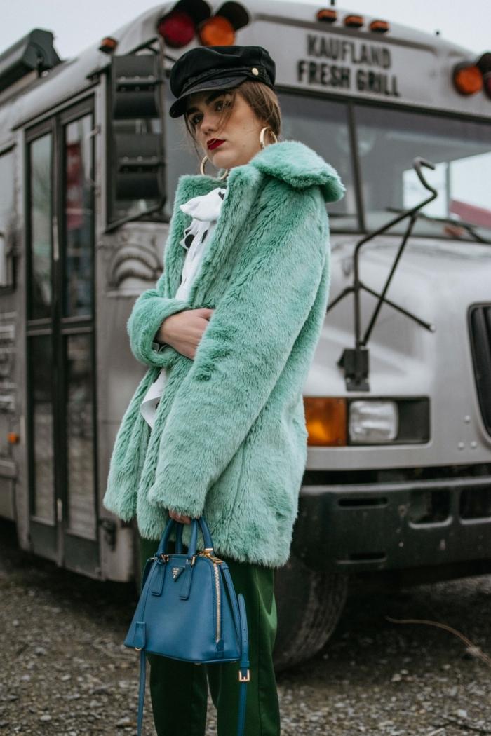 manteau vert, sac bleu, casquette noire, pull blanc, créoles en or, rouge à lèvres vif, pantalon vert