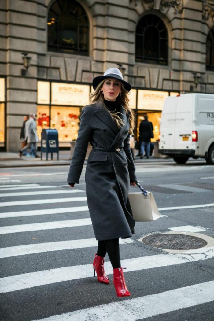 jeune femme se promène dans la cité, manteau veste gris, chapeau feutre, bottes rouges