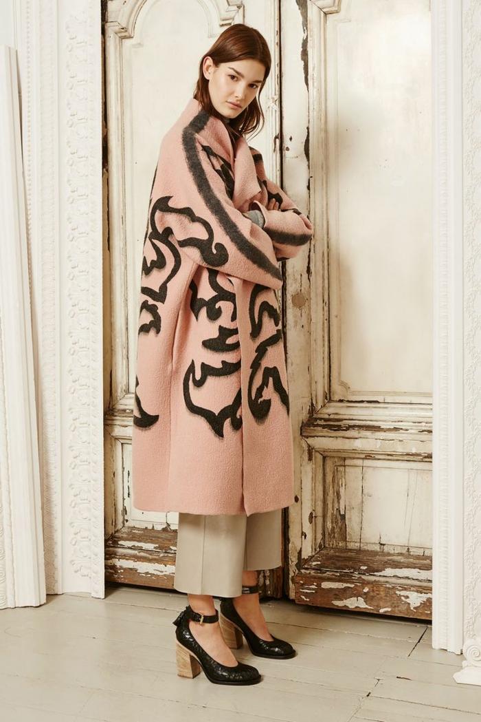 manteau en rose nude, motifs noirs, pantalon blanc, chaussures vitages aux talons épais, grande porte peinte blanche
