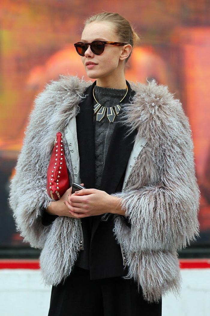 femme d'affaires, collier statement aux pendentifs géométriques, sac rouge, manteau gris poilu