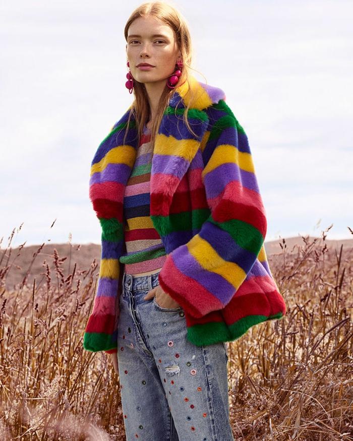 manteau poilu bariolé, rayures multicolores, jeans décorés, grands boucles d'oreilles fuchsia