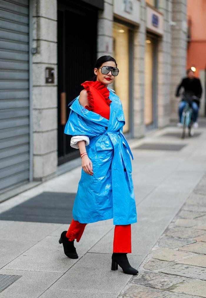 manteau imperméable bleu, pantalon rouge, blouse rouge, lunettes surdimensionnées, femme moderne