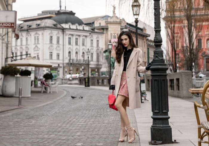 jolie rue et bâtiments à jolie architecture, sandales talons fins, jupe rose, sac rouge