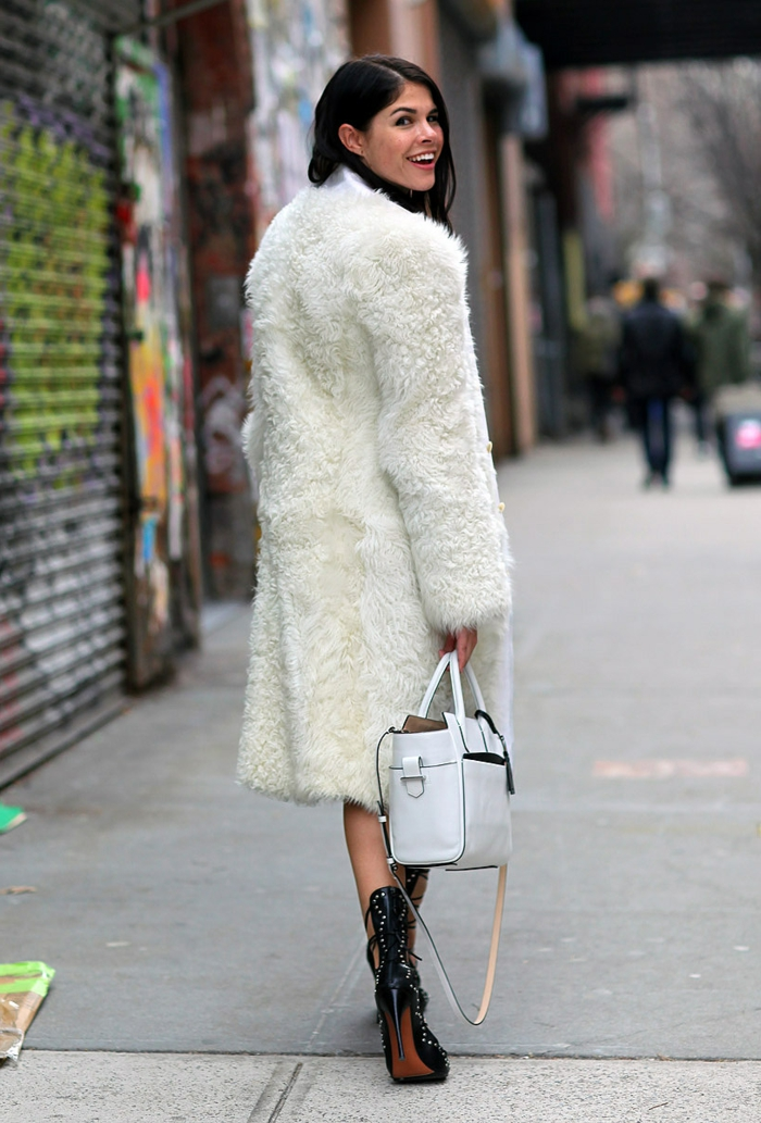 femme aux cheveux noirs, manteau blanc long, bottes extravagantes, sac statement blanc
