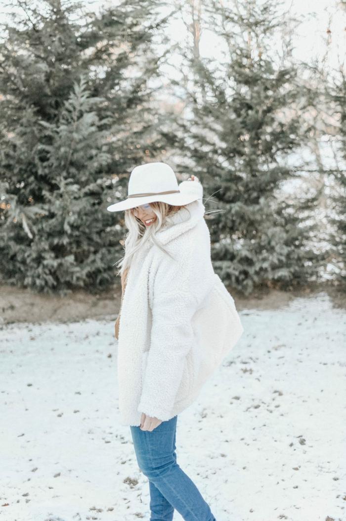 femme dans la forêt, manteau poilu blanc, jeans bleus, pins enneigés, paysage d'hiver